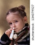 Young girl using nasal spray looking worried - stock photo
