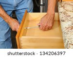 Closeup of a cabinet installer installing drawer hardware on new kitchen cabinets. Horizontal format, man is unrecognizable. - stock photo