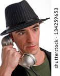 Headshot of a Caucasian Male Wearing a Fedora Style Hat and Talking on the Phone - stock photo