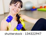 Young cheerful smiling woman exercising with dumbbells - stock photo