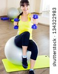 Young cheerful smiling woman exercising with dumbbells and fitball - stock photo