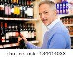 Man in a supermarket choosing a wine bottle - stock photo