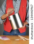 Closeup of a paint store employee holding a paint can ready to hand to a customer. Vertical format, man is unrecognizable. - stock photo
