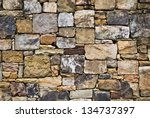 A beautifully designed rock wall. Many colors and sizes mixed for interest. - stock photo