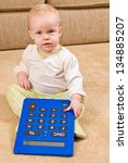 A young baby in a pair of generic pajamas sitting on the floor with a large, over-sized calculator. - stock photo