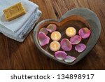 spa composition with stone heart filled with water rose petals and floating candles - stock photo