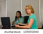Two business woman in a conference room working on a laptop - stock photo