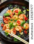 Shrimps and chopstick on pan with fresh herbs - stock photo