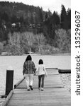 A black and white image of a mother and daughter walking on the boardwalk at Hauser Lake, Idaho. - stock photo