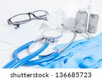 Mask, stethoscope, gloves, pills, glasses and a bandage on a white background - stock photo