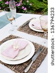 Table setting with napkin and rustic trimmings in the garden - stock photo