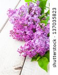 Lilac branch on wooden table - stock photo