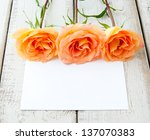 Three beautiful yellow orange roses with card for your text. - stock photo