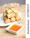 Plate of Thai spring rolls appetizer with garnish. - stock photo