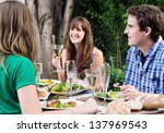 Group of friends talking and enjoying themselves at a outdoor garden party with food and wine drinks - stock photo