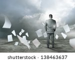 Business concept - Paperwork flying around a businessman. - stock photo