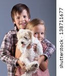 Happy kids holding their new pet - a small fluffy dog - stock photo