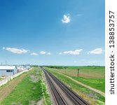 railroad in green fields and blue sky - stock photo
