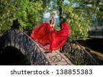Romantic portrait of the woman in airy red dress dancing on the bridge, sea view on background - stock photo