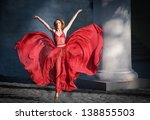 Romantic portrait of the woman in airy red dress dancing on cobblestone pavement - stock photo