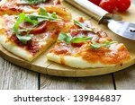 Pepperoni pizza with tomato sauce and herbs on a wooden board - stock photo