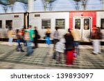 waiting people at the station when the train arrives. The people are in motion blur while the train is sharp because of panning the camera - stock photo