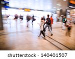 people in motion blur walking in a railway station - stock photo