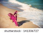 Woman in airy crimson dress dancing on the beach - stock photo