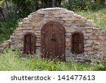 Stone Wall of Root Cellar with Small Door and Windows or Hobbit House in a Hillside - stock photo
