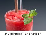 Red fruit flavored frozen cocktail or smoothie beverage with straw and stirring stick. - stock photo