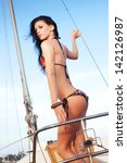 Portrait of a gorgeous long-haired brunette in stylish swimsuit standing on the aft of a sailing yacht. Sunny summer day. Bikini fashion. Outdoor shot - stock photo