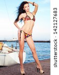 Portrait of a gorgeous long-haired brunette in stylish swimsuit standing on the pier (quay) near a yacht. Sunny summer day. Bikini fashion. Outdoor shot - stock photo