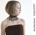 Head shot of beautiful girl posing in studio in bare shoulder top and neck jewelry - stock photo