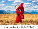 Portrait of a smiling woman in red clothes in the wheat field - stock photo
