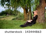Portrait of a beautiful sad woman sitting under a tree with an opened book - stock photo