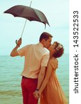 Summer vacation concept. Couple standing on beach near water, holding black umbrella and kissing each other. Hipster style. Outdoor shot - stock photo