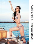 Portrait of a gorgeous long-haired brunette in stylish swimsuit standing on the aft of a sailing yacht. Sunny summer evening. Bikini fashion. Outdoor shot - stock photo