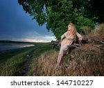 Blond woman on the river bank at sunset - stock photo