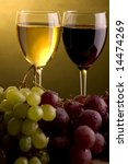 a glass of red and white wine and green and red grape - stock photo