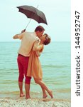 Summer vacation concept. Couple standing on beach near water, holding black umbrella and kissing each other. Hipster style. Happy together. Outdoor shot - stock photo