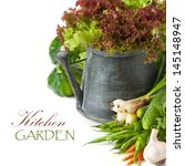 Fresh kitchen garden vegetables and watering can on a white background. - stock photo