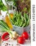 Fresh kitchen garden vegetables on an old wooden board. - stock photo