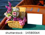 Picnic basket on an antique boat. White sign for your own advertising use. - stock photo