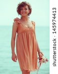 Hipster bride concept: portrait of a beautiful young woman with great tan wearing trendy wedding dress, posing and standing at the seaside. Girl holding bouquet. Outdoor shot - stock photo