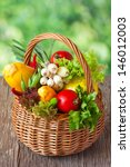 Basket of fresh ripe vegetables on an old garden board. - stock photo