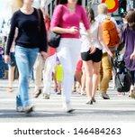 Motion blurred pedestrians crossing sunlit street - stock photo