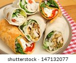 Plate of wrap sandwiches filled with chicken and cheese. - stock photo