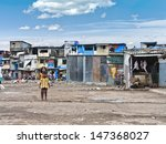 MUMBAI, INDIA - SEPTEMBER 13: Some unidentified children are playing on a blank area of a slum infront of their homes on September 13, 2008 in Mumbai, India. Beside a butcher is waiting for customers. - stock photo