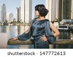 attractive young woman standing in front of river - stock photo