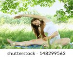 Young woman in a park doing stretching exercises - stock photo